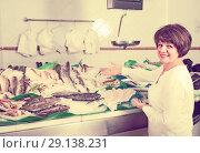 Купить «Young female customer buying fish», фото № 29138231, снято 25 октября 2016 г. (c) Яков Филимонов / Фотобанк Лори