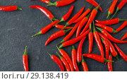Купить «red chili or cayenne pepper on stone surface», видеоролик № 29138419, снято 20 сентября 2018 г. (c) Syda Productions / Фотобанк Лори