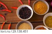Купить «bowls with different spices on wooden table», видеоролик № 29138451, снято 20 сентября 2018 г. (c) Syda Productions / Фотобанк Лори