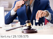 Купить «Young lawyer playing chess to train his court strategy and tacti», фото № 29139575, снято 31 июля 2018 г. (c) Elnur / Фотобанк Лори