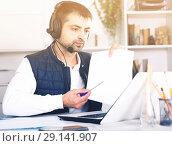 Купить «Young man call centre operator with headphones working», фото № 29141907, снято 25 декабря 2017 г. (c) Яков Филимонов / Фотобанк Лори