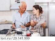 Купить «Confused woman with elderly father reading work manual on mixer tap», фото № 29141999, снято 19 июня 2018 г. (c) Яков Филимонов / Фотобанк Лори