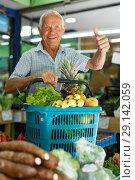 Купить «Satisfied man with basket filled with fruits and vegetables», фото № 29142059, снято 16 июня 2018 г. (c) Яков Филимонов / Фотобанк Лори