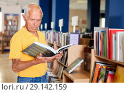 Купить «Focused elderly man looking for information in books in bookstore», фото № 29142159, снято 11 июня 2018 г. (c) Яков Филимонов / Фотобанк Лори