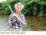 Купить «Mature fisherman with rod at riverside», фото № 29142223, снято 10 июня 2018 г. (c) Яков Филимонов / Фотобанк Лори