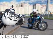 Купить «Мотоциклетный шлем висит на руле припаркованного мотоцикла на фоне мотоциклиста, сидящего на чоппере», фото № 29142227, снято 15 сентября 2018 г. (c) Кекяляйнен Андрей / Фотобанк Лори