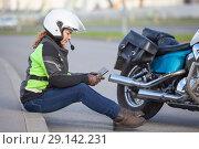 Купить «Девушка в мотоциклетной экипировке сидит на бордюре возле мотоцикла и смотрит в смартфон», фото № 29142231, снято 15 сентября 2018 г. (c) Кекяляйнен Андрей / Фотобанк Лори