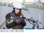Купить «Женщина мотоциклистка читает сообщение в телефоне, сидя на мотоцикле», фото № 29142235, снято 15 сентября 2018 г. (c) Кекяляйнен Андрей / Фотобанк Лори