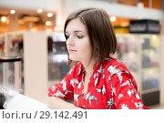 Купить «Young girl with a bob haircut sitting in a coffee shop in a shopping center», фото № 29142491, снято 27 сентября 2018 г. (c) Константин Шишкин / Фотобанк Лори