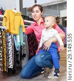 Купить «Young mother is choosing new clothes for her son in the kid store.», фото № 29149535, снято 18 апреля 2018 г. (c) Яков Филимонов / Фотобанк Лори