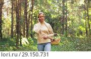 Купить «woman with mushrooms calling on cellphone in woods», видеоролик № 29150731, снято 24 сентября 2018 г. (c) Syda Productions / Фотобанк Лори