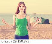 Купить «Young woman in blue T-shirt is standing and practicing asana», фото № 29150875, снято 4 августа 2017 г. (c) Яков Филимонов / Фотобанк Лори