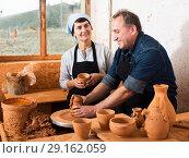 Купить «Couple among the pottery», фото № 29162059, снято 12 октября 2016 г. (c) Яков Филимонов / Фотобанк Лори