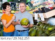 Купить «Adult male and female are choosing green melons in the store.», фото № 29162251, снято 22 октября 2017 г. (c) Яков Филимонов / Фотобанк Лори