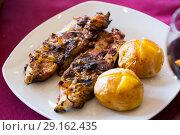 Купить «Broiled pig trotters with baked potatoes», фото № 29162435, снято 15 октября 2018 г. (c) Яков Филимонов / Фотобанк Лори