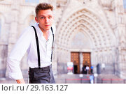 Купить «young European guy in shirt and trousers with suspenders walking around city», фото № 29163127, снято 27 июня 2018 г. (c) Татьяна Яцевич / Фотобанк Лори