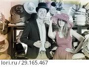 Купить «Glad woman and man trying on fashion hats», фото № 29165467, снято 2 мая 2017 г. (c) Яков Филимонов / Фотобанк Лори