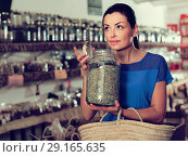 Купить «adult female take a smell natural dried herbs sold by weight in eco shop», фото № 29165635, снято 13 июня 2017 г. (c) Яков Филимонов / Фотобанк Лори