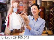 Купить «Female choosing carpet samples», фото № 29165643, снято 22 ноября 2017 г. (c) Яков Филимонов / Фотобанк Лори