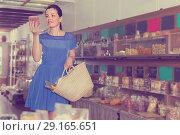 Купить «Girl is choosing sweet dry fruits», фото № 29165651, снято 13 июня 2017 г. (c) Яков Филимонов / Фотобанк Лори