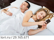 Купить «Beautiful young wife texting with lover on smartphone», фото № 29165671, снято 31 мая 2020 г. (c) Яков Филимонов / Фотобанк Лори