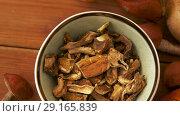 Купить «dried mushrooms in bowl on wooden background», видеоролик № 29165839, снято 30 сентября 2018 г. (c) Syda Productions / Фотобанк Лори