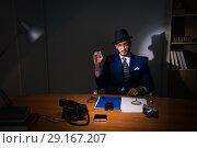 Купить «Detective sitting in dark room in vintage concept», фото № 29167207, снято 13 июля 2017 г. (c) Elnur / Фотобанк Лори