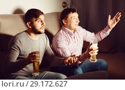 Купить «Two men watching tv with anxious uncertainty», фото № 29172627, снято 7 февраля 2018 г. (c) Яков Филимонов / Фотобанк Лори