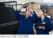 Купить «portrait of expert woman standing with clipboard and talking to winemaker in cellar», фото № 29172835, снято 15 октября 2018 г. (c) Яков Филимонов / Фотобанк Лори