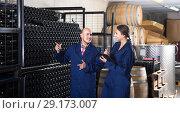 Купить «portrait of expert woman standing with clipboard and talking to winemaker in cellar», фото № 29173007, снято 15 октября 2018 г. (c) Яков Филимонов / Фотобанк Лори
