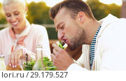 Купить «man with friends eating burger at rooftop party», видеоролик № 29179527, снято 26 сентября 2018 г. (c) Syda Productions / Фотобанк Лори