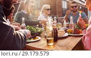 Купить «friends having dinner or bbq party on rooftop», видеоролик № 29179579, снято 26 сентября 2018 г. (c) Syda Productions / Фотобанк Лори