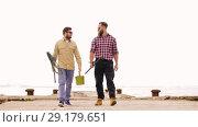 Купить «happy friends with fishing rods walking along pier», видеоролик № 29179651, снято 28 сентября 2018 г. (c) Syda Productions / Фотобанк Лори