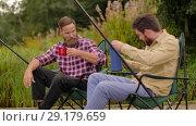 Купить «friends fishing and drinking tea from thermos», видеоролик № 29179659, снято 28 сентября 2018 г. (c) Syda Productions / Фотобанк Лори