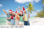 Купить «friends in santa hats over beach on christmas», фото № 29183891, снято 30 июня 2018 г. (c) Syda Productions / Фотобанк Лори