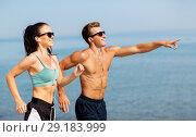 Купить «couple with earphones running along on beach», фото № 29183999, снято 1 августа 2018 г. (c) Syda Productions / Фотобанк Лори