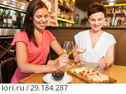 Купить «women eating snacks at wine bar or restaurant», фото № 29184287, снято 25 июня 2018 г. (c) Syda Productions / Фотобанк Лори