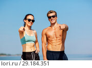 Купить «happy couple in sports clothes and shades on beach», фото № 29184351, снято 1 августа 2018 г. (c) Syda Productions / Фотобанк Лори