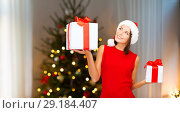 Купить «smiling woman in santa hat with christmas gifts», фото № 29184407, снято 15 августа 2013 г. (c) Syda Productions / Фотобанк Лори