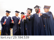 Купить «happy students in mortar boards with diplomas», фото № 29184539, снято 24 сентября 2016 г. (c) Syda Productions / Фотобанк Лори