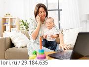 Купить «working mother with baby calling on smartphone», фото № 29184635, снято 12 мая 2018 г. (c) Syda Productions / Фотобанк Лори