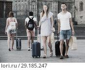 Купить «Smiling traveling man and woman walking together with luggage», фото № 29185247, снято 22 июня 2017 г. (c) Яков Филимонов / Фотобанк Лори