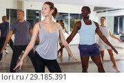 Купить «Group of active young people enjoying practicing modern dance together», фото № 29185391, снято 30 июля 2018 г. (c) Яков Филимонов / Фотобанк Лори