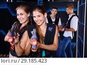 Купить «Two smiling girls posing with plastic laser pistols and two guys in background in laser tag room», фото № 29185423, снято 27 августа 2018 г. (c) Яков Филимонов / Фотобанк Лори