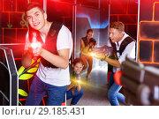 Купить «Portrait of excited guy with laser pistol playing laser tag in a», фото № 29185431, снято 27 августа 2018 г. (c) Яков Филимонов / Фотобанк Лори