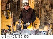 Купить «Кузнец на рождественской ярмарке в Варшаве кует подкову, Польша», фото № 29185855, снято 27 декабря 2014 г. (c) Наталья Волкова / Фотобанк Лори