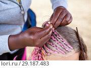Купить «Руки афро американской женщины плетут дреды на голове девочки», фото № 29187483, снято 19 июля 2018 г. (c) Кекяляйнен Андрей / Фотобанк Лори