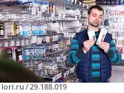 Купить «thoughtful male customer choosing fishing hooks near stand in the sports shop», фото № 29188019, снято 16 января 2018 г. (c) Яков Филимонов / Фотобанк Лори
