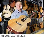 Купить «Mature man choosing acoustic guitar», фото № 29188223, снято 18 сентября 2017 г. (c) Яков Филимонов / Фотобанк Лори