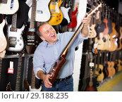 Купить «Man choosing electric guitar», фото № 29188235, снято 18 сентября 2017 г. (c) Яков Филимонов / Фотобанк Лори